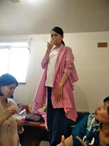 TAKSUAMANATの服を試着している女性