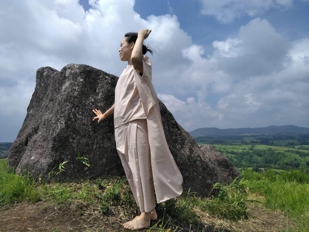 TAKSU AMANATのお洋服を着て丘に立つ女性