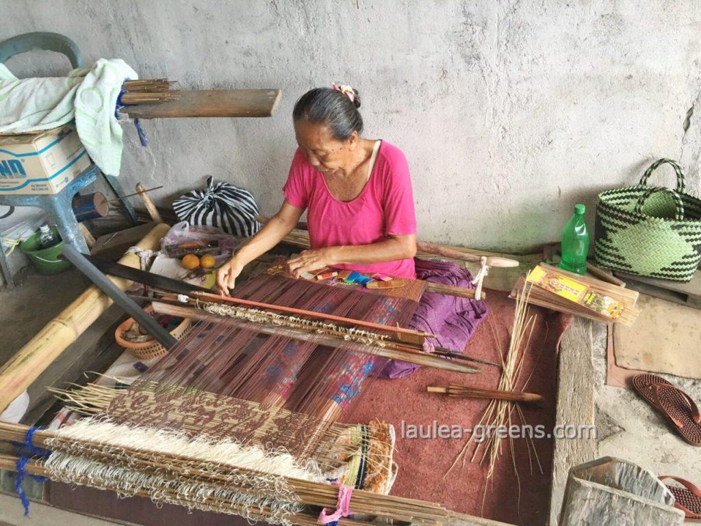 腰機で布を織る織子さん